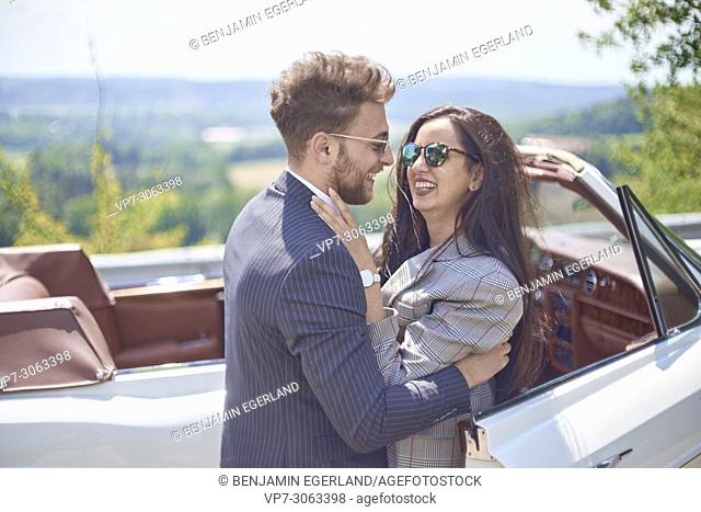 Happy couple in front of luxury oldtimer car. Turkish ethnicity. Blogger Adem Bayalan. Bavaria, Germany