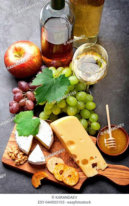 White wine, grape, bread and cheese on stone table
