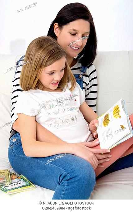 Little girl sitting on her mother's lap, and reading a book in her bedroom