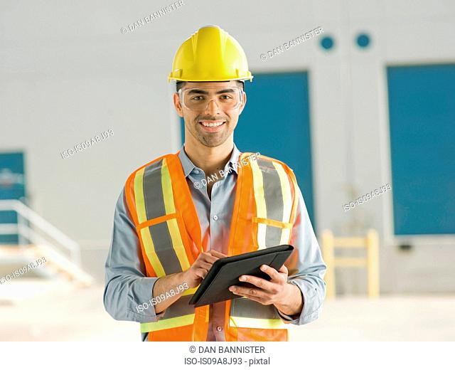 Mid adult construction worker using digital tablet, portrait