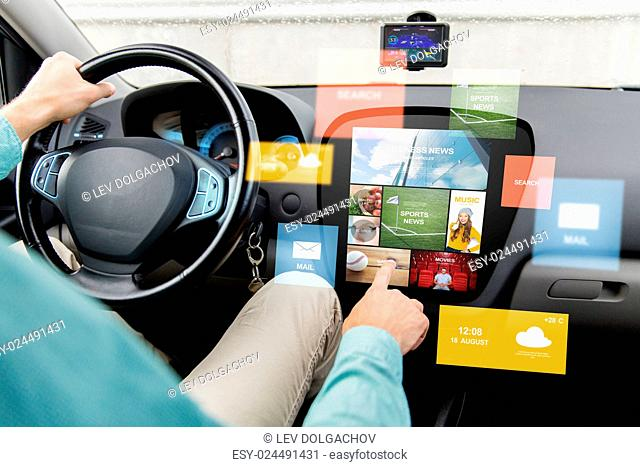 transport, modern technology, media and people concept - close up of man driving car with news on board computer screen