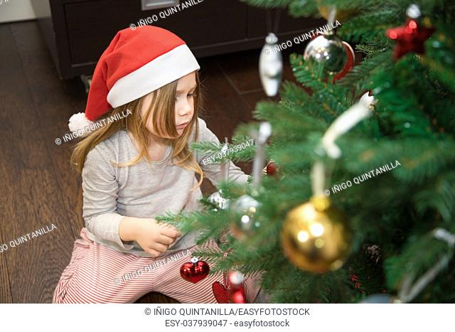 four years blonde cute girl with red Santa Claus hat, kneeling on the floor at home, decorating Christmas tree