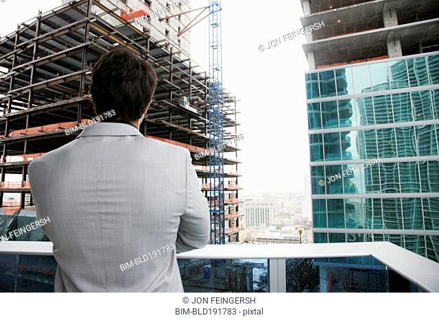 Hispanic businessman looking at skyscraper construction from balcony