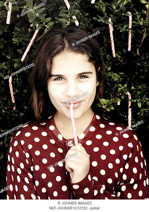 Portrait of girl eating candy cane from tree