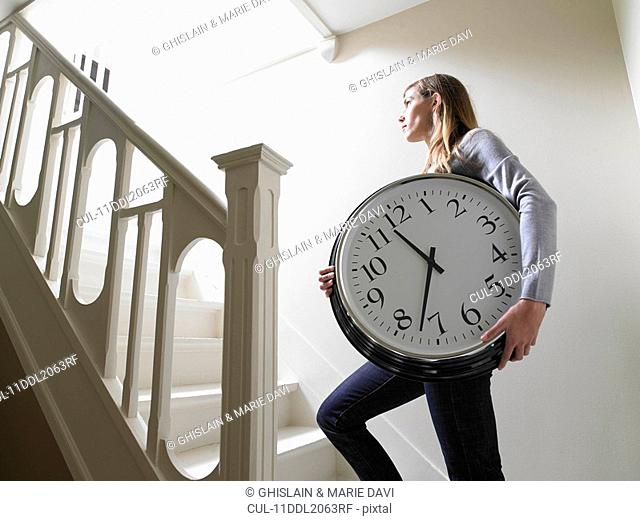 Woman climbing the stairs with a clock