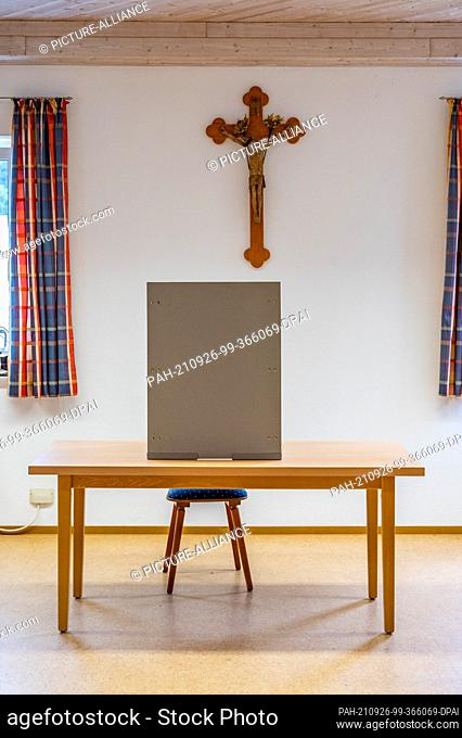 26 September 2021, Bavaria, Inkofen: An empty voting booth on a table in front of a wooden cross in a polling station. Photo: Armin Weigel/dpa