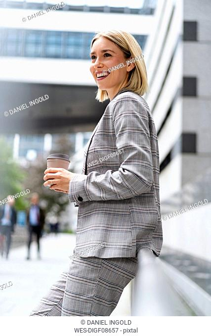 Happy young businesswoman with takeaway coffee in the city
