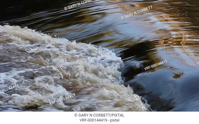 Water in a river flowing over a ledge and making a back wash and foam