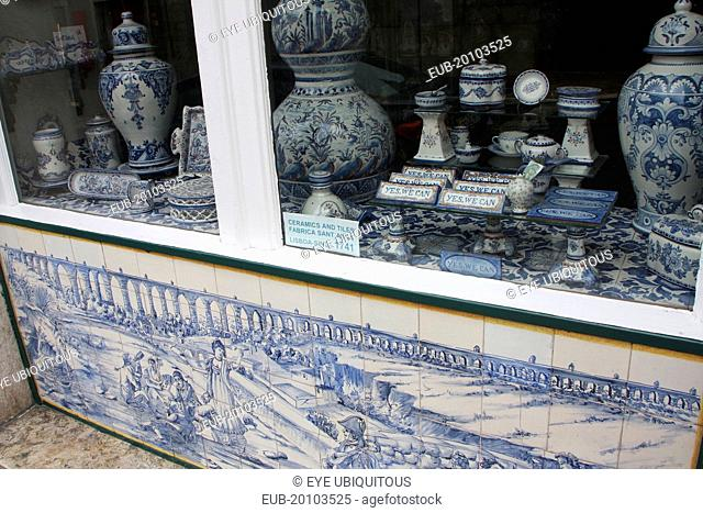 Chiado district. Shopfront with an azulejo tiled exterior wall and window display of ceramics and tiles