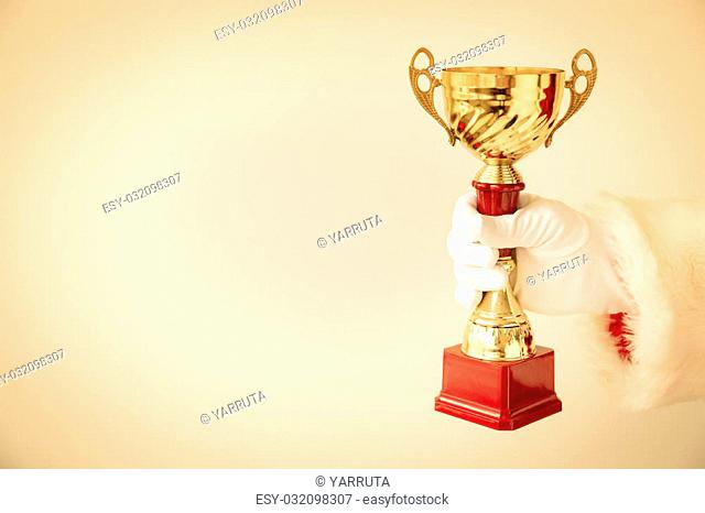 Santa Claus holding gold trophy in hands. Christmas holiday concept