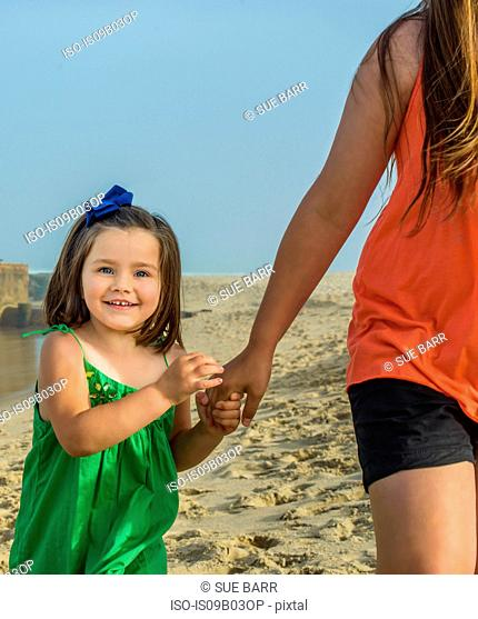 Cute girl holding teenage sisters hand on beach, Asbury Park, New Jersey, USA