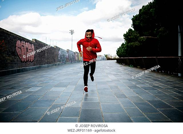 Smiling young man wearing red hoodie running in the city
