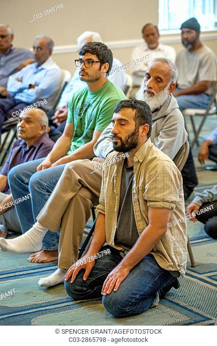 Listening to an Iman's sermon or Khutbah, Muslim men gather for Friday afternoon Abrahamic prayers during religious services at an Anaheim, CA, mosque
