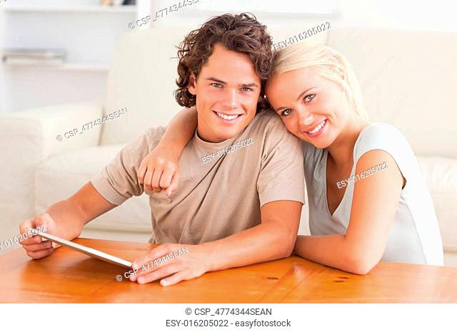 Hugging cute couple with a tablet
