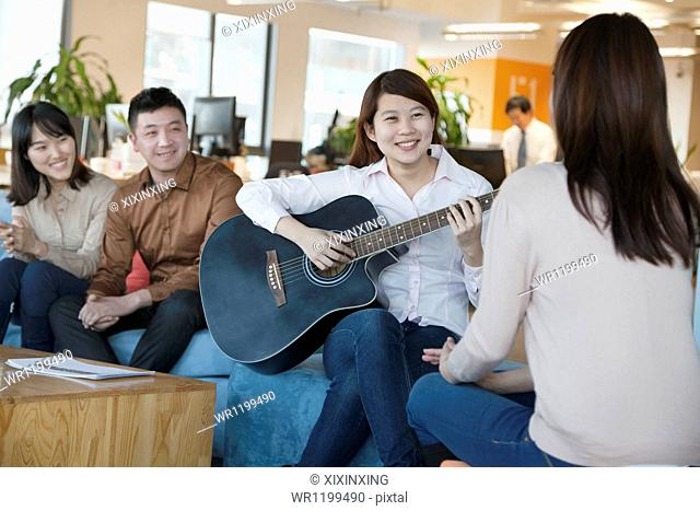 Young Office Worker Playing Guitar to Colleagues