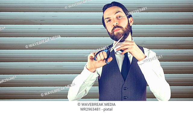 Confident hipster cutting beard against wall