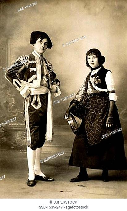 Young couple standing in traditional Spanish costumes, c.1910