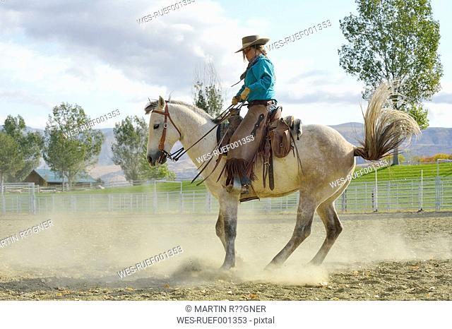 USA, Wyoming, Cowgirl working with horse