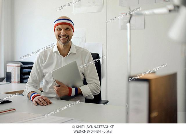 Businessman sitting in office, wearing sweat bands, holding laptop