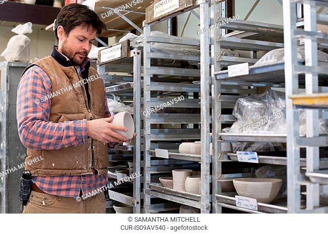 Potter in storage room quality checking unfinished clay pots