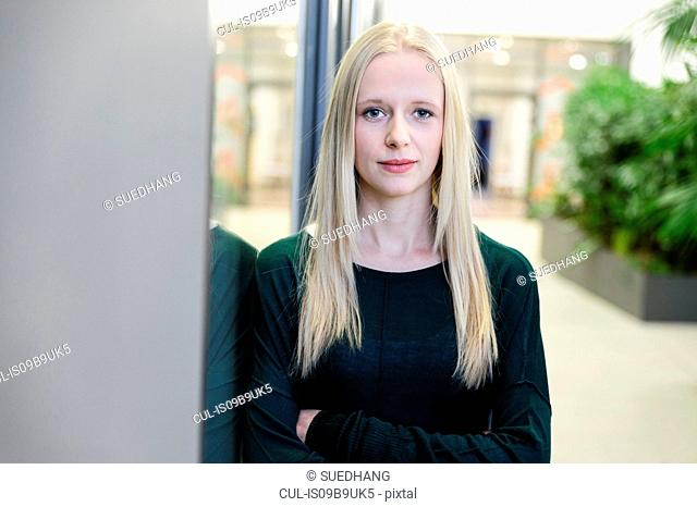 Portrait of young businesswoman with arms folded at office entrance