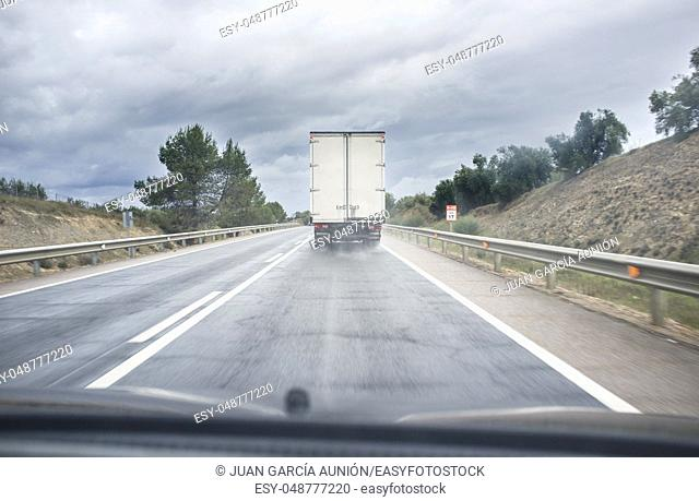 Driving behind slow truck on local road a rainy day. View from the inside of the car