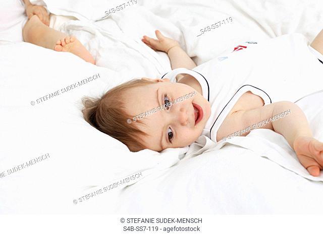 Toddler in underwear lying in bed, Berlin, Germany