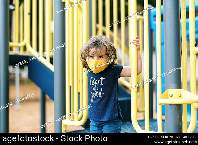 A little toddler girl wearing her mask for protection from covid-19