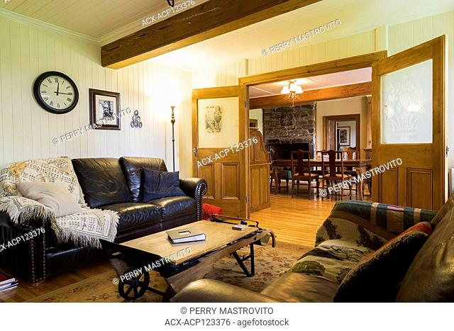 Music room with dark brown leather sofas and old grain scale table inside an old circa 1752 Canadiana style fieldstone house, Quebec, Canada