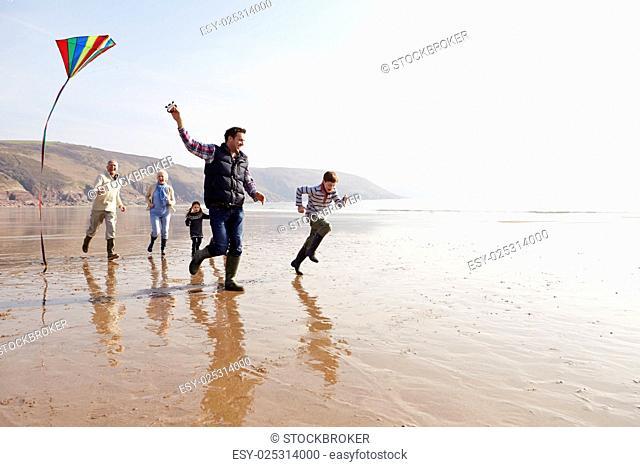Multi Generation Family Flying Kite On Winter Beach