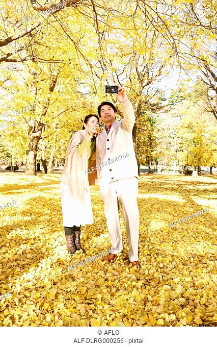 Senior Japanese couple taking pictures in a city park in Autumn