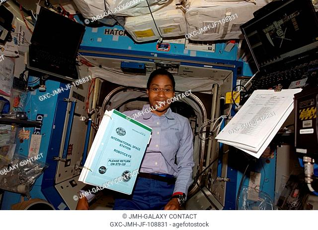 Astronaut Stephanie Wilson, STS-120 mission specialist, poses for a photo as a procedures handbook floats freely nearby in the Destiny laboratory of the...