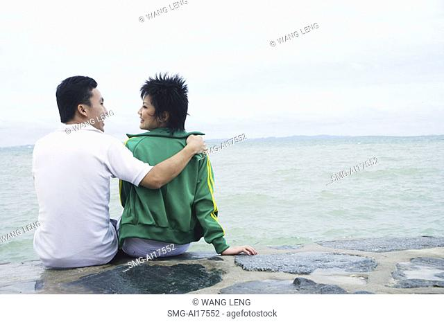 Couple sitting on breakwater, embracing, rear view