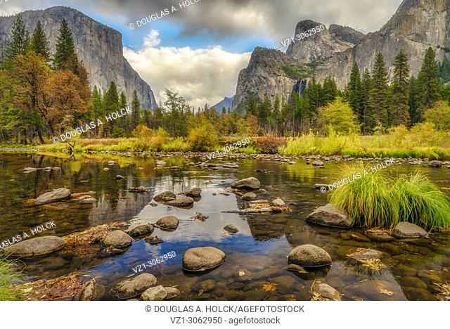 Lazy Merced River on a fall day reflects clouds over El Capitan and Bridalveil Fall of Yosemite National Park, California, USA