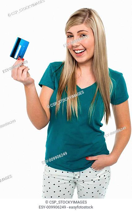 Joyous teenager displaying credit card