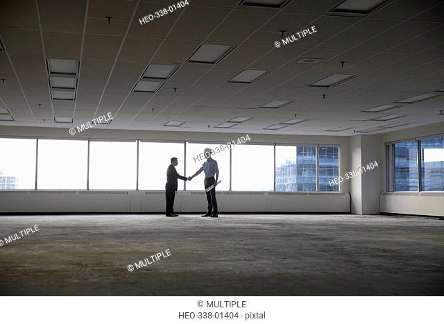 Contractor and businessman shaking hands in unfinished, empty urban open plan office
