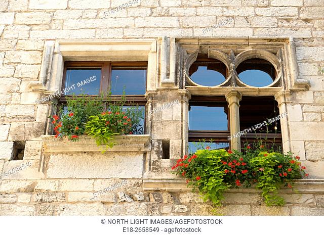 France, Midi-Pyrénées, Martel. Stone windows and window boxes in medieval village