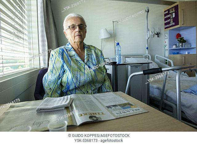 Tilburg, Netherlands. Senior adult woman in her eighties, sitting inside her hospital bedroom recovering from a hip operation