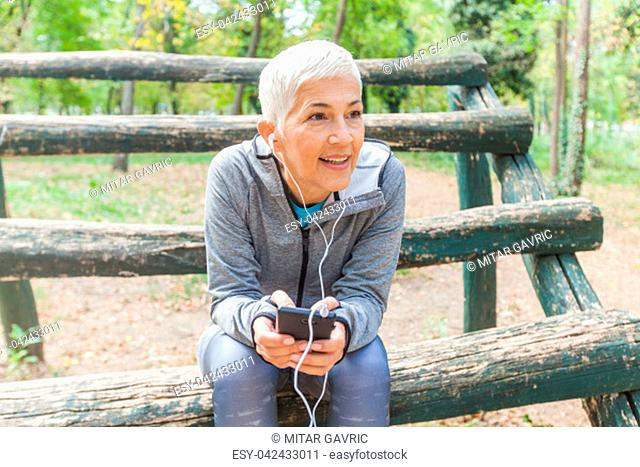 Senior Woman Relax Listening Music With Phone After Jogging In Forest. Healthy Lifestyle Workout Outdoor