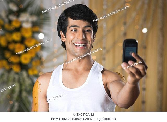 Man taking a picture of himself with a mobile phone and smiling