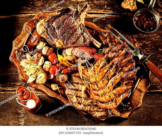 Variety of barbecue beef, shrimp and various vegetables served on table with oil, ketchup and seasonings
