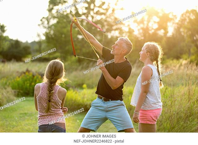 Father showing daughters how to use bow and arrows