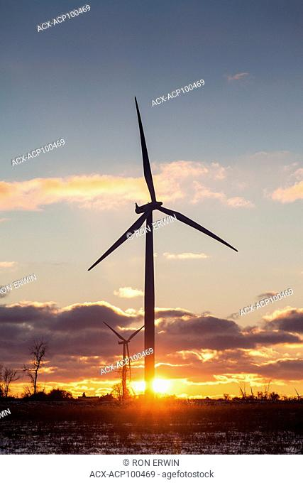 The sun setting behind wind turbines on Wolfe Island, Ontario, Canada