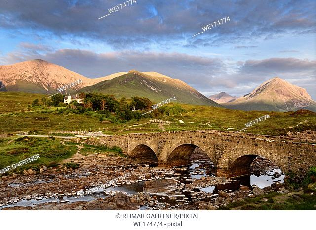 Sligachan Old stone Bridge over River Sligachan with Beinn Dearg Mhor and Marsco peak of Red Cuillin mountains at sunset Isle of Skye Scotland UK