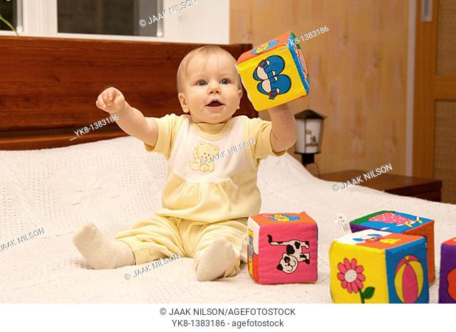 Happy Eight Month Old Infant Girl Playing With Cubes on Bed