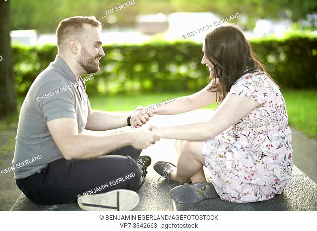 enamoured couple sitting together on ping-pong table, holding hands