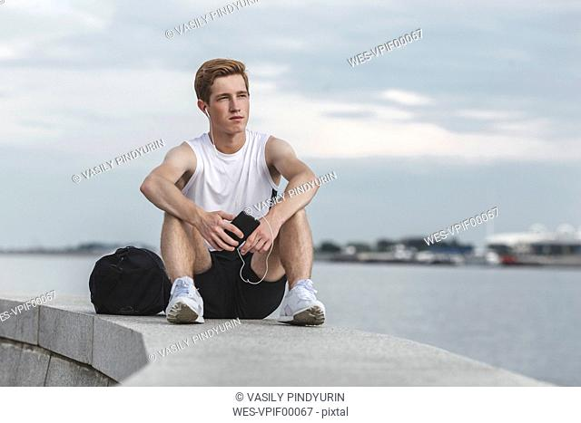 Young athlete sitting on a wall at riverbank with cell phone and earphones