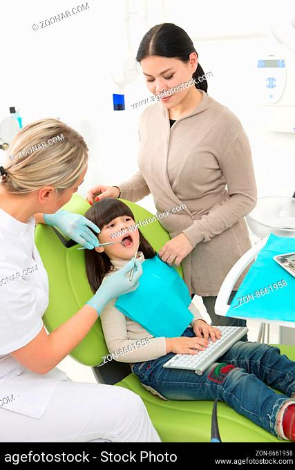 Dentist examining little girl#39;s teeth at the dentist#39;s office. Young mother standing near her daughter