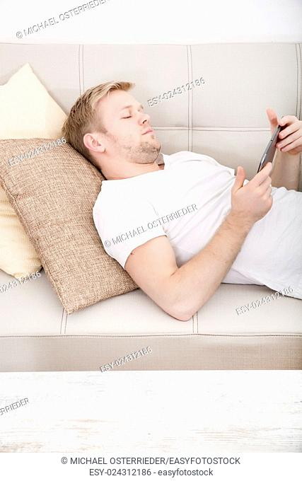 Young man using a tablet at home on the couch