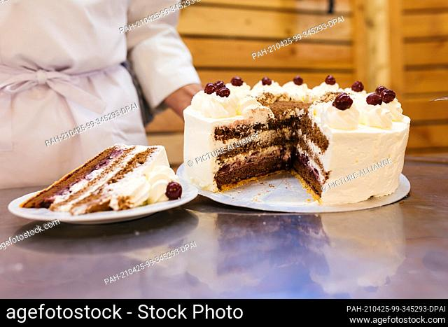 25 April 2021, Baden-Wuerttemberg, Todtnauberg: A piece of Black Forest cake lies on a plate next to a Black Forest cake in the run-up to a livestream of the...